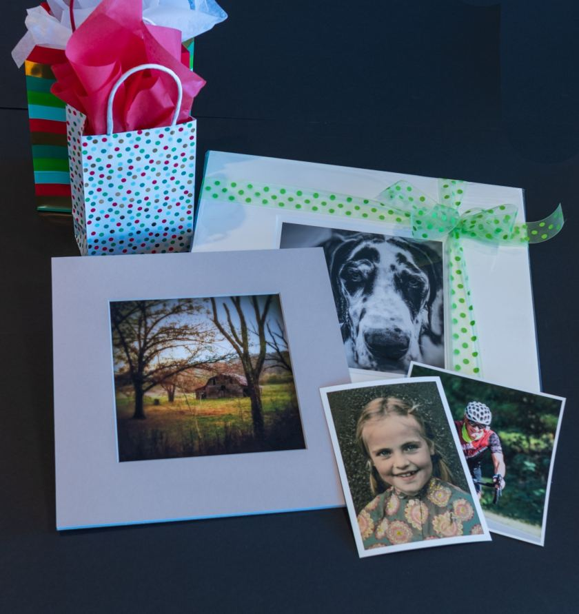 An assortment of photos are displayed on a counter to show the various printing styles and sizes.