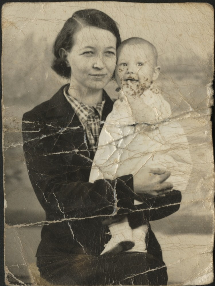 An old photo with crack and discoloration. It pictures a woman holding a child.