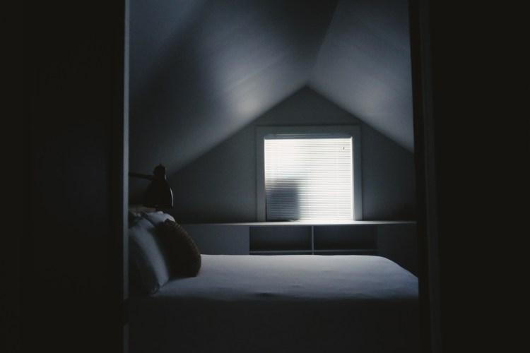white bed frame beside attic window