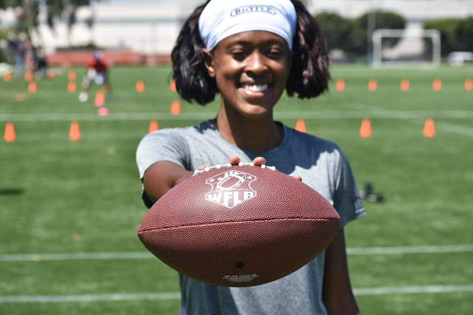 Woman from WFLA Women's Football League holding a football—The Birmingham Bombshells will be our local team