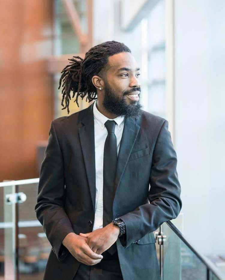 man wearing a suit and locs