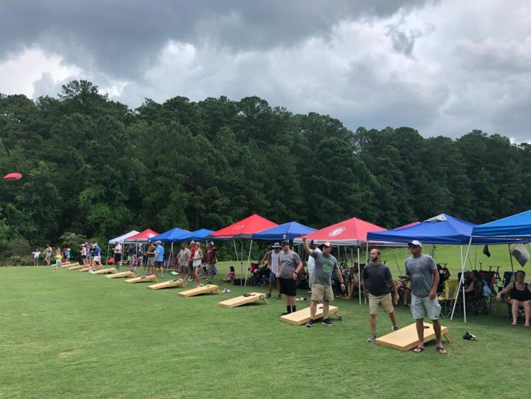 Lineup of people playing cornhole with viewers in tents - community sports in Birmingham