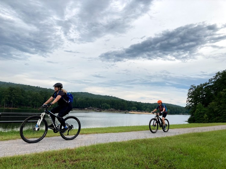 Two people biking in front of a lake