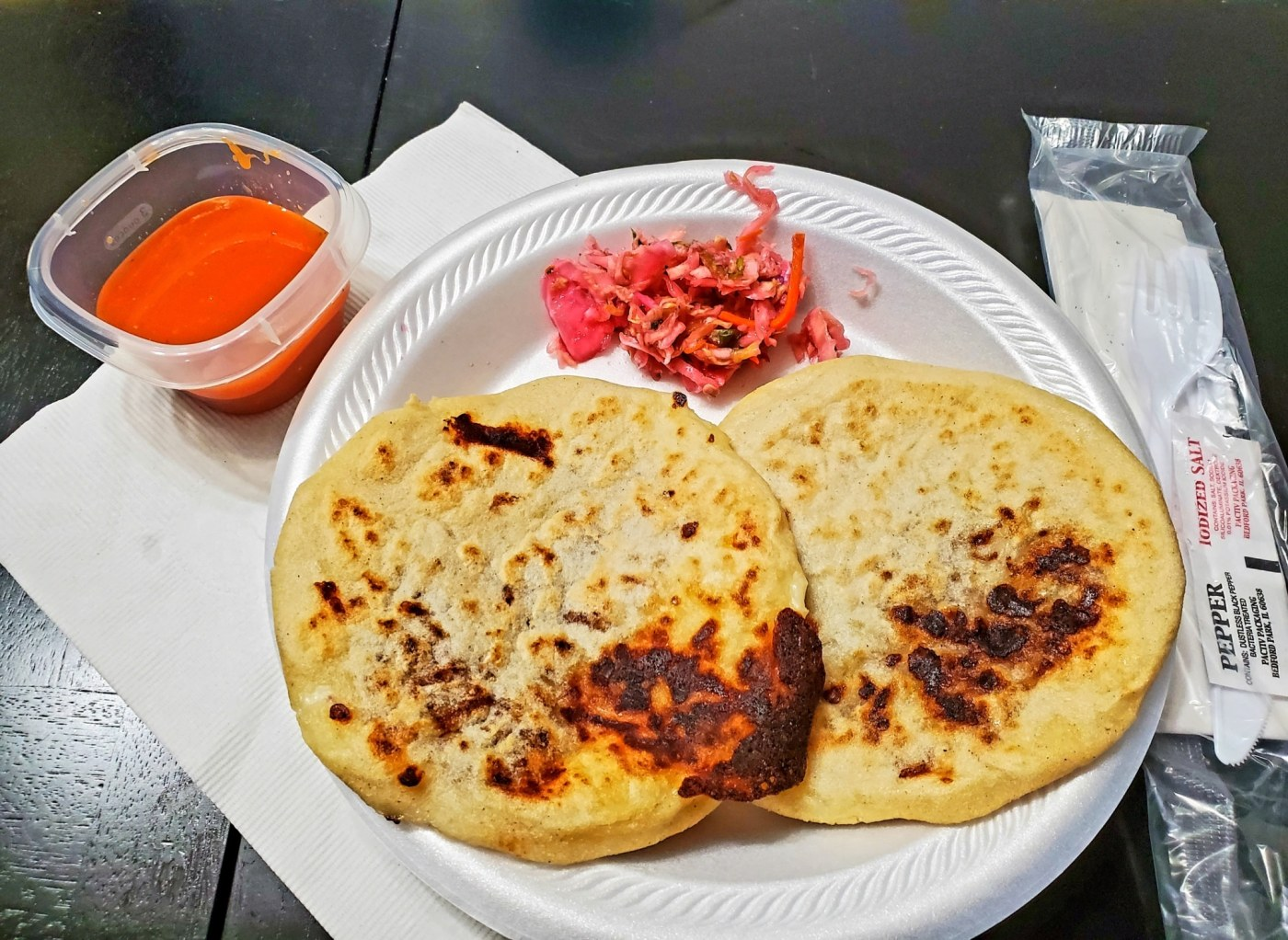 Plate with two pupusas on it and condiments on the side.