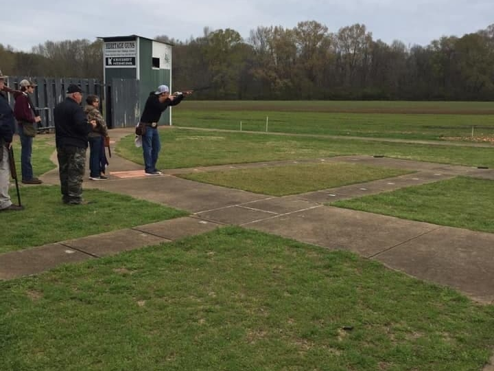 One man aiming his gun while others stand in line behind him at Red Eagle Skeet and Trap Club