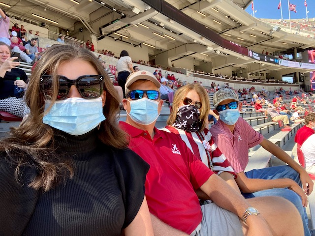 A family wearing masks in the stadium at an Alabama football game.