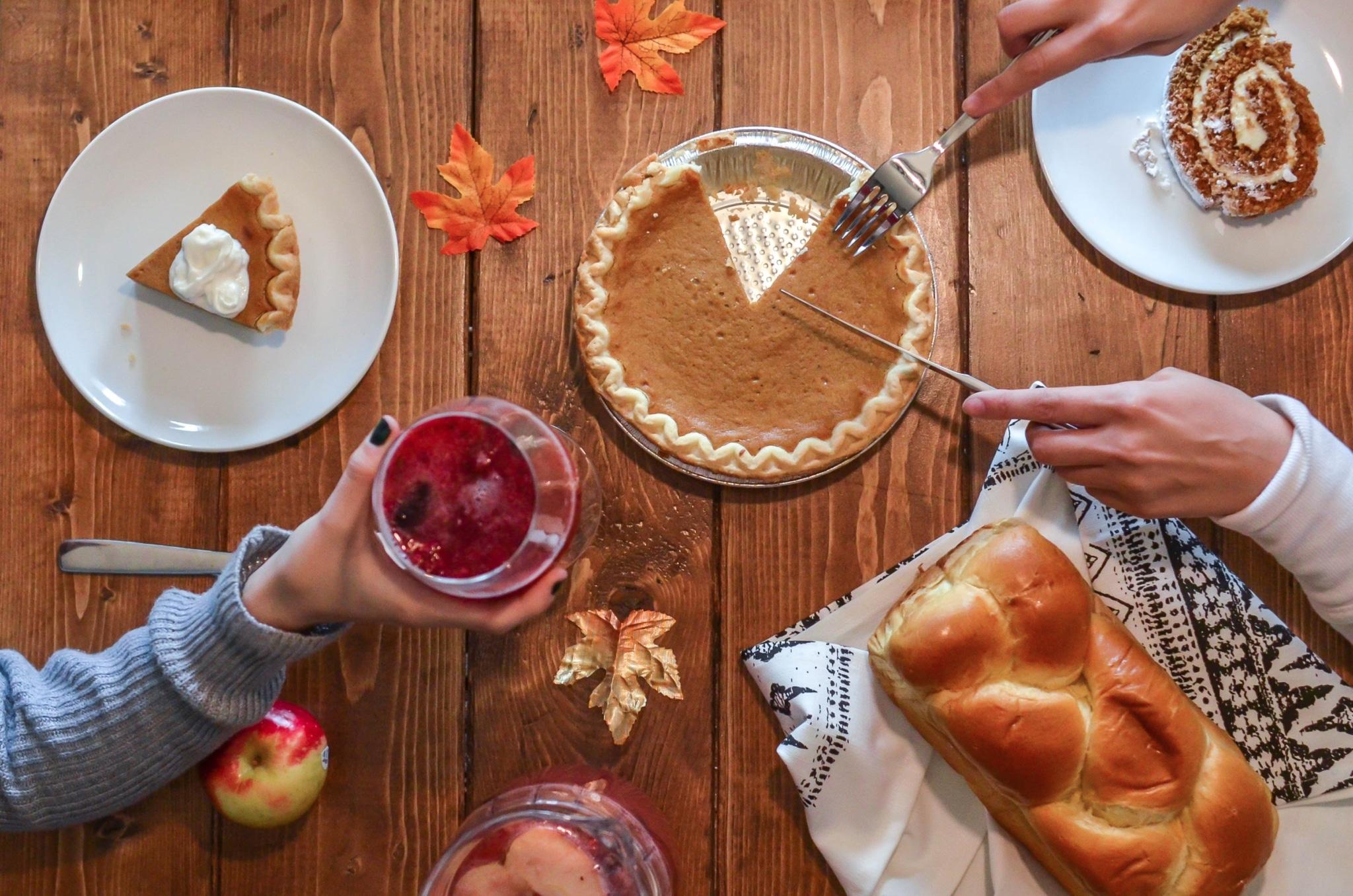 person slicing pie beside bread