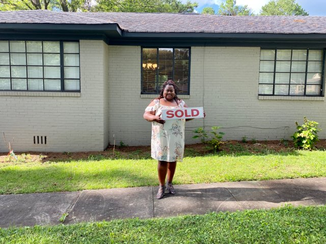 Homebuyer in front of her new home