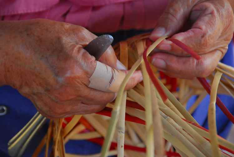 Native American hands weaving a basket