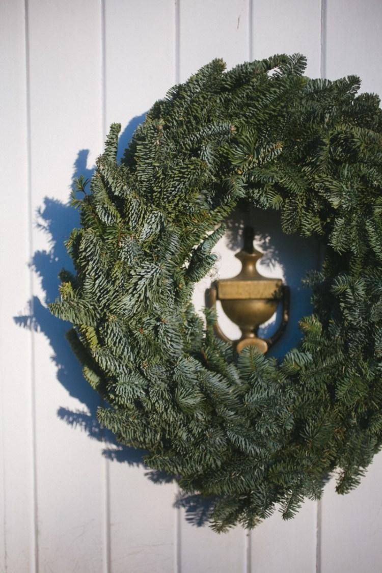 green wreath around brass door knocker