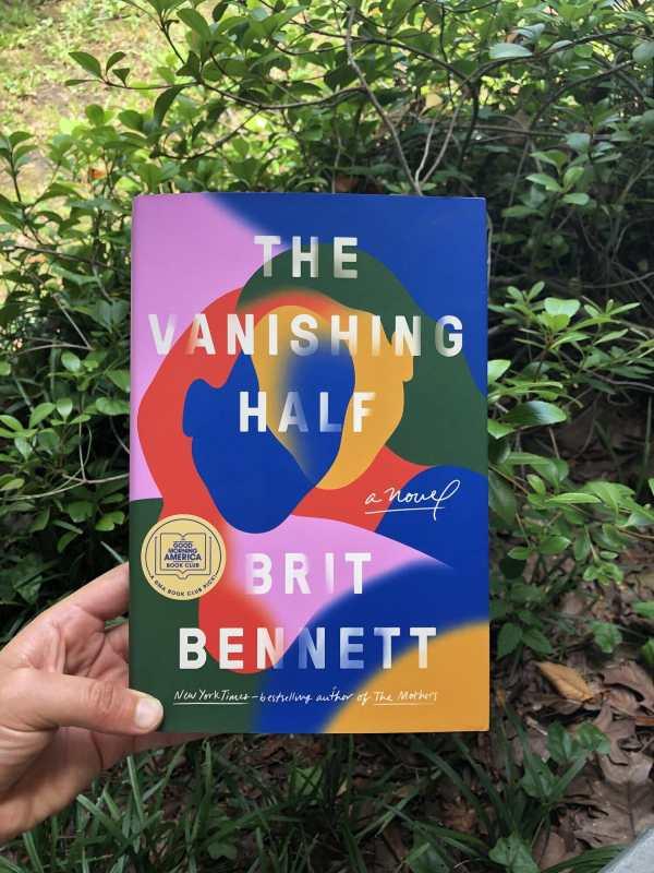 The Vanishing Half held in front of bushes