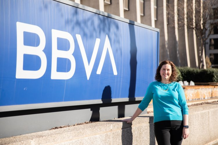 Karla Blevins in front of the BBVA sign near the Rotary Trail—she's a graduate of the UNA MBA program