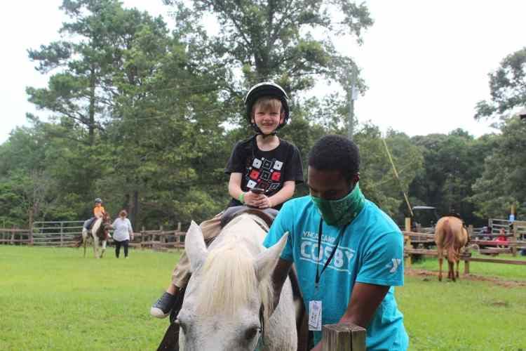 camper on a horse with a counselor at YMCA Camp Cosby