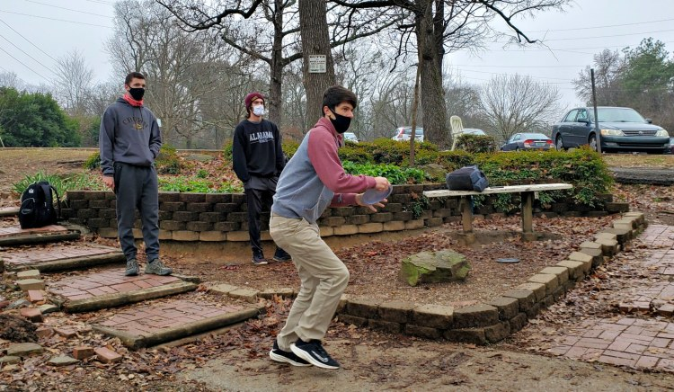 Three disc golf players throwing disc at George Ward Park.