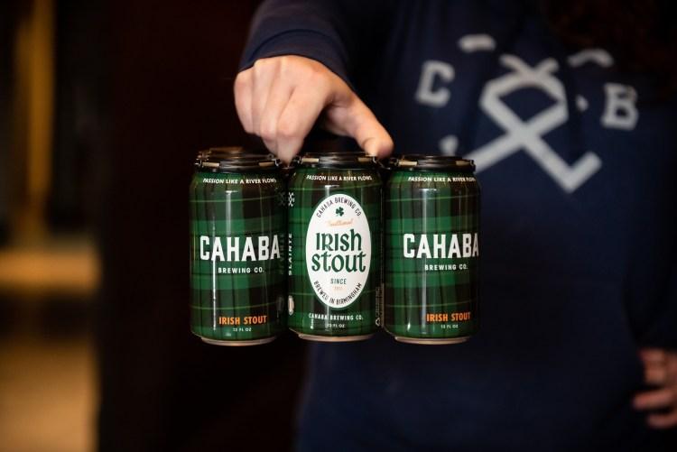 Man holding six pack of Irish Stout