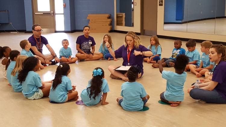 Group of children gathered in a circle around counselor