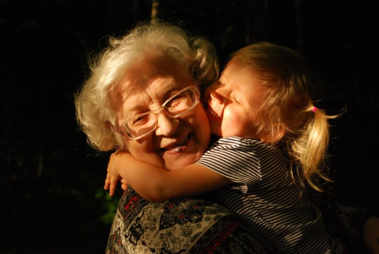 woman in black and white striped shirt hugging girl in black and white striped shirt, help for seniors in Central Alabama