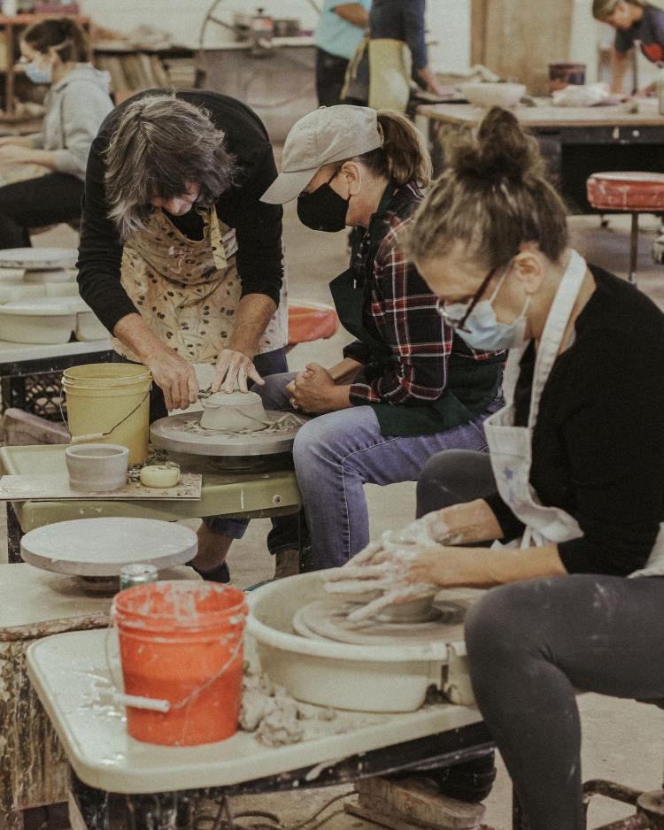 people wheel throwing pottery