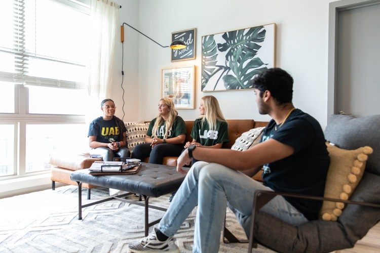 UAB students laughing in living room