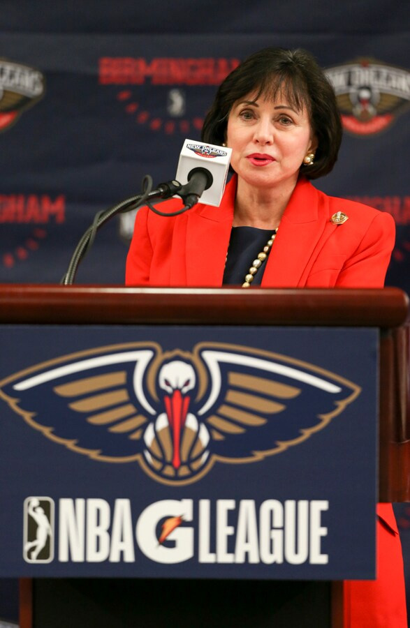 woman speaking into microphone behind New Orleans Pelicans podium