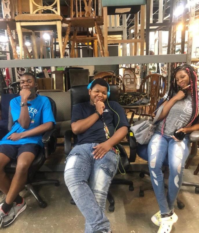 Three students sit down and pose at Sozo Trading Company