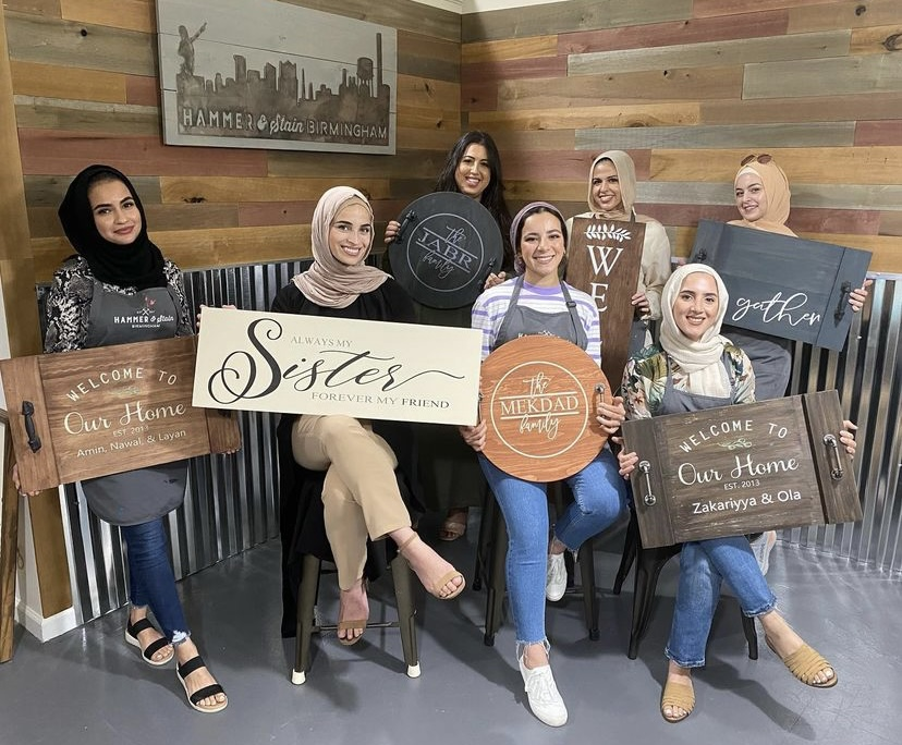 group of women holding wooden home decor signs