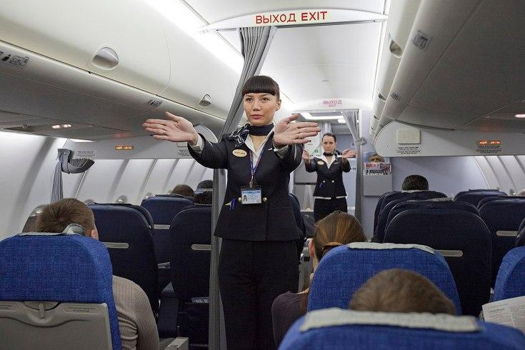 1200px-Flight_attendants_performing_a_pre-flight_safety_demonstration_on_an_Aeroflot_Sukhoi_Superjet