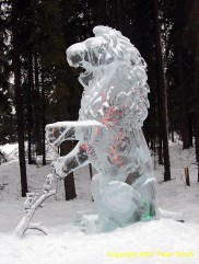 A sculpture of a lion and a pair of mouse on a ice tree limb.