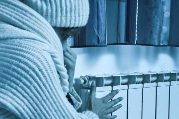 Woman freezing at home, checking the radiator