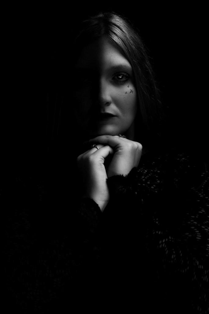 Photographie d'un femme avec la moitier du visage dans le noir photo prise par bhf Photo