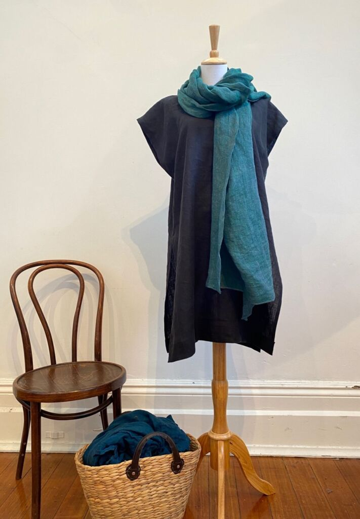 Yarrow tunic in black linen, displayed on a mannequin with a teal scarf draped around the neck. Next to the mannequin is a chair and a basket of mending. The Yarrow tunic is a sustainable, ethically made garment.