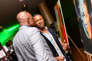 17. Ice Nweke speaking to a guest during the art exhibition