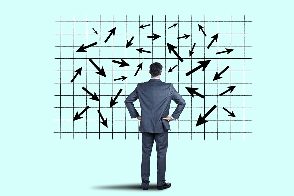 A businessman places his hand on his head in confusion as he looks up at a large chart that shows unpredictable sales or performance trends represented by many arrows pointing in different directions.