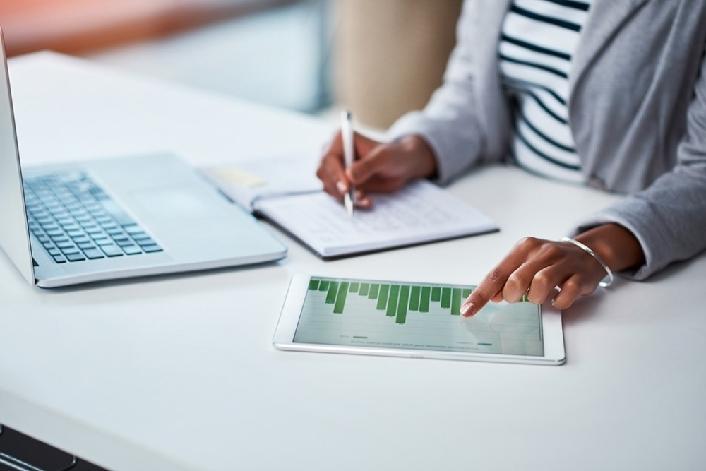 Shot of a businesswoman using a digital tablet with graphs on it in a modern office