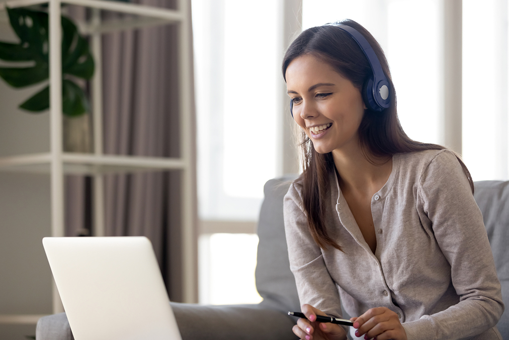 Happy young woman in Bluetooth headphones sit on couch, on laptop, having skype or web conversation on computer