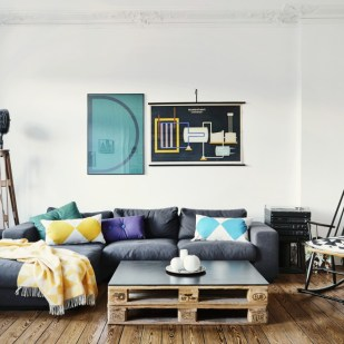 Seating area in period apartment with DIY coffee table made from euro pallets, vintage studio lamp and framed posters on wall