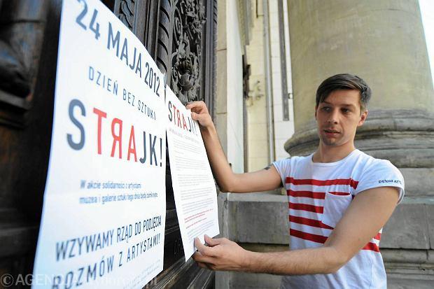 Rok 2012. Karol Sienkiewicz przykleja na drzwiach galerii Zachęta plakat wzywający rząd do zajęcia się fatalną sytuacją finansowo-ubezpieczeniową artystów