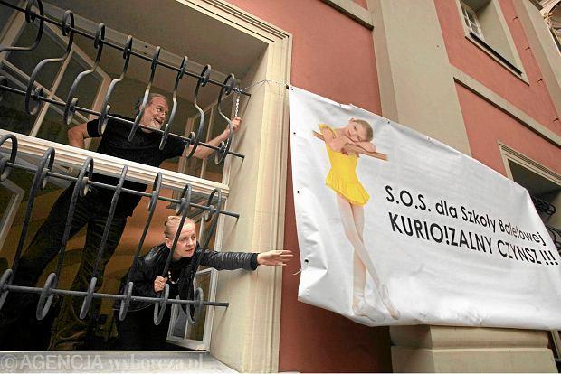 Dyrektor szkoły baletowej w Poznaniu Mirosław Różalski i kierownik artystyczny Krystyna Frąckowiak  przy banerze zawieszonym w proteście przeciw wysokiemu czynszowi, którego zażądała kuria  za korzystanie z budynku, 2013