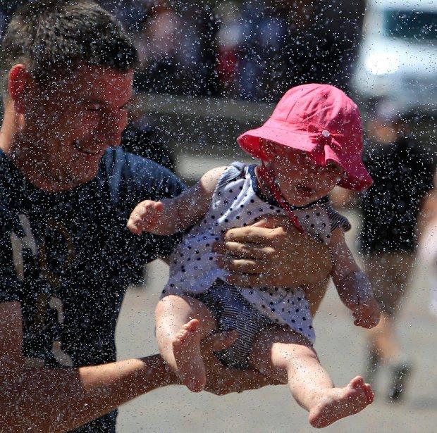 Piątek, 3 lipca 2015. Upał w Warszawie, mężczyzna chłodzi dziecko pod kurtyną wodną.