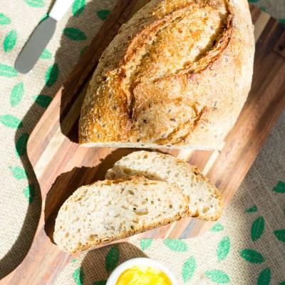 Pão de grãos de fermentação natural, servido sobre uma tábua, semi fatiado, com um pote de manteiga ghee e uma faca de passar manteiga