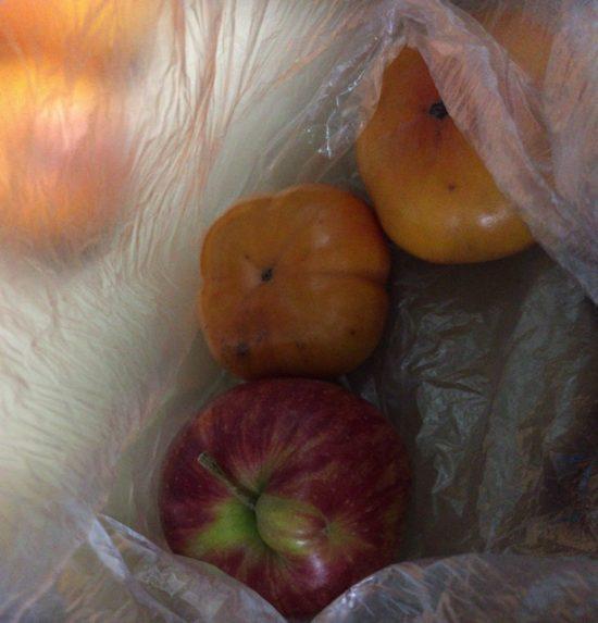 固い柿をりんごと一緒にビニール袋に入れる画像