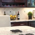 Bianco romano cherry cabinets with travertine backsplash tile
