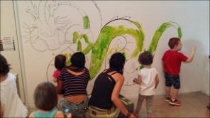 Nens pintant mural drac