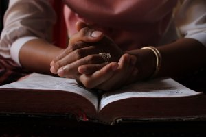 a disciplined woman praying with her open bible