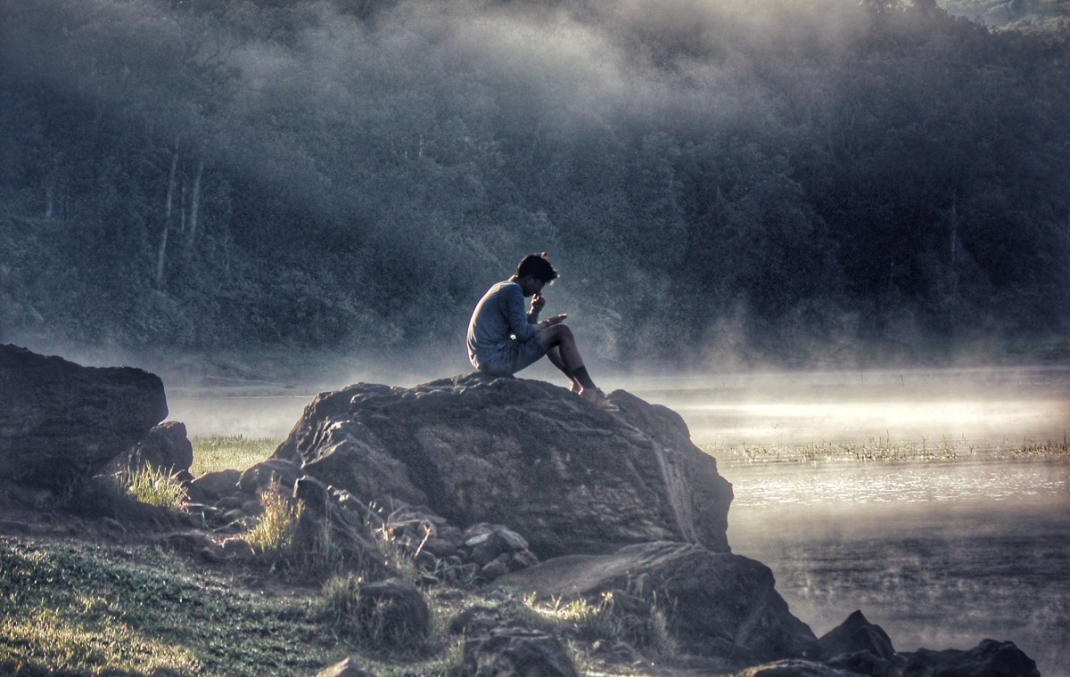 man reflecting on life while sitting on Rock