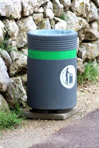 Modern concrete trash can with freshly put nylon bag inside positioned on stone tile next to traditional stone wall and paved sidewalk