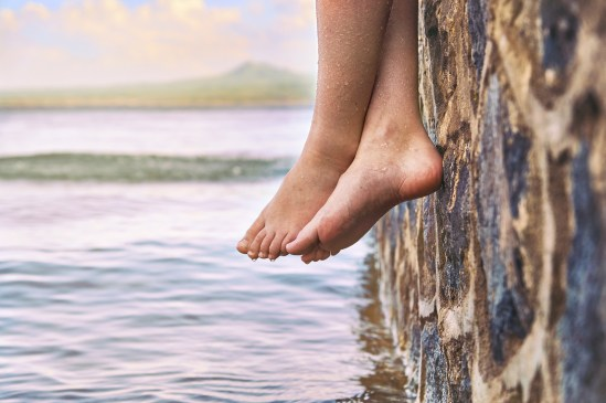 Wet bare girl's feet dangling from the stone jetty