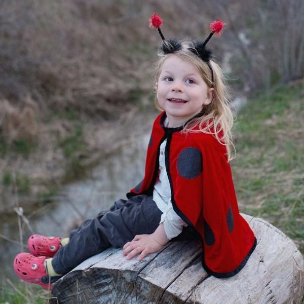 Cape de coccinelle rouge à pois noir portée par un enfant qui porte le serre-tête avec des antennes à pompons