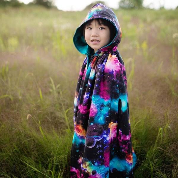 Grande cape galaxie portée par un enfant de profil avec la capuche