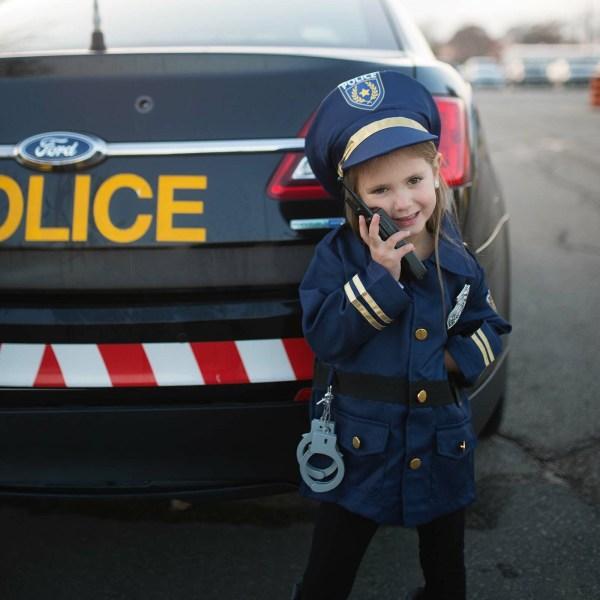 une petite fille porte le déguisement de pompier devant une voiture de police